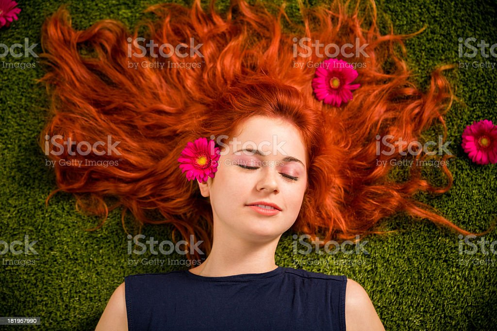 Relaxing girl on grass with red hair royalty-free stock photo
