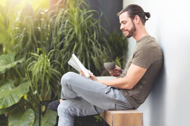 Relajante hombre hipster leyendo un libro. - foto de stock