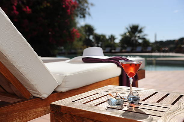 relaxing in a luxury hotel by the pool soft drink in a beach chair by the pool of a luxury hotel poolside stock pictures, royalty-free photos & images