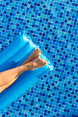 Cropped shot of woman legs on a floating mattress in swimming pool. Female sunbathing on swimming mattress in pool.