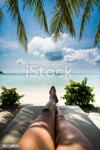 Unrecognizable woman relaxing in a shade during summer day at tropical beach.