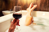 Relaxing in bathtub with foam and glass of red wine