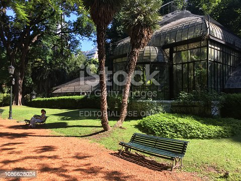 Buenos Aires, Argentina - December 22, 2018: Woman sitting on bench and checking her mobile phone in the in the peaceful and quiet atmosphere to the Botanical Garden. Lots of people come here during the day to rest or just enjoy this natural environment in the heart of the city