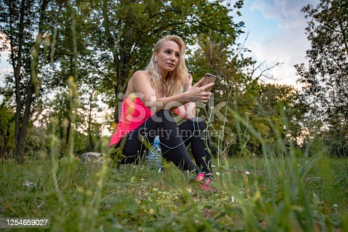 Woman in nature relaxing and listening music. She wear In-ear Headphones and listen music from her mobile phone. Bright and warm colors and realistic situation. Photo is represent ordinary day after work or over weekend and connection between relaxing music and nature.