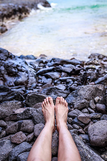 Relaxing legs on the rocks ,near the beach stock photo
