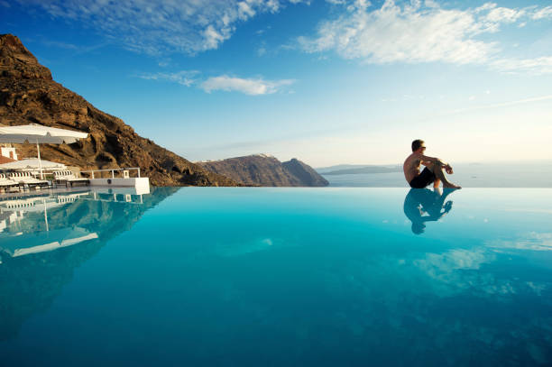 Relaxing Man Sitting Edge Luxury Resort Infinity Pool Santorini Greece Man sits on edge of infinity pool looking out over view of Santorini caldera, Greece infinity pool stock pictures, royalty-free photos & images