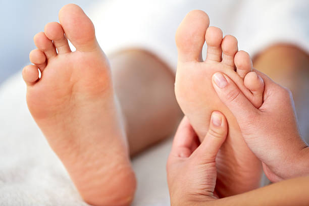 Relaxing massage Close-up of female hands pampering feet foot massage stock pictures, royalty-free photos & images