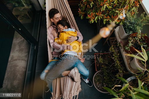 Photo of a young couple having a relaxing moment in a hammock on a terrace of their apartment