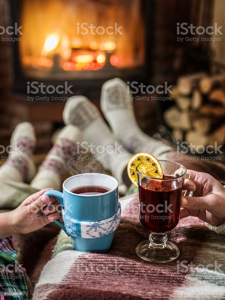 Relaxing near fireplace with a cup of hot drink. stock photo