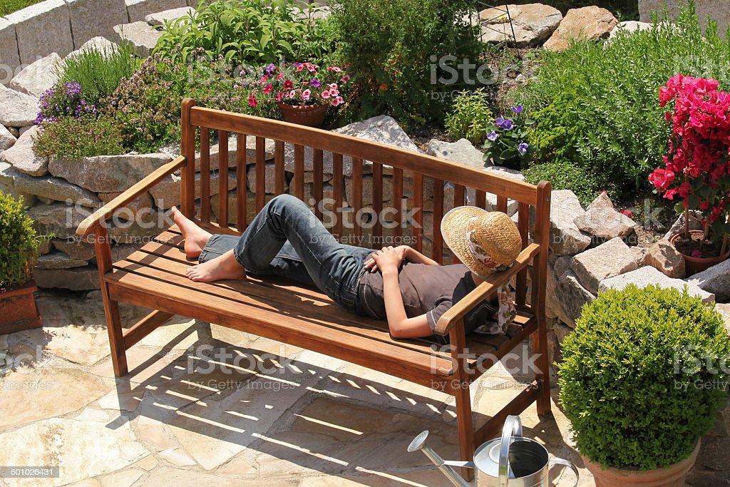 Relaxing on a garden bench stock photo