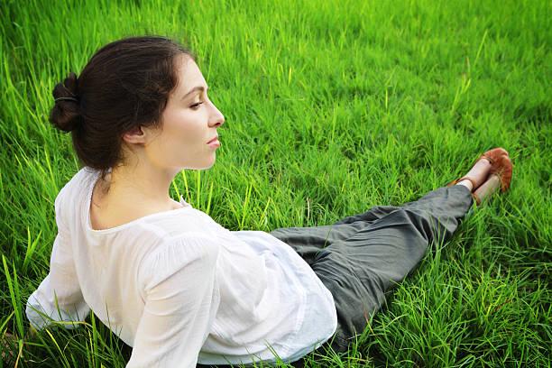 entspannend auf gras field - leinenhosen frauen stock-fotos und bilder