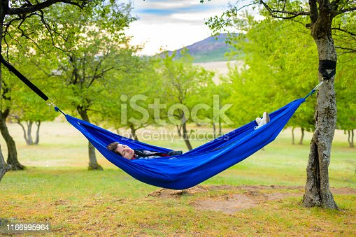 Beautiful young woman relaxing on hammock, summer day