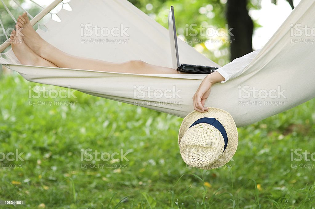 Relaxing on hammock with a laptop stock photo