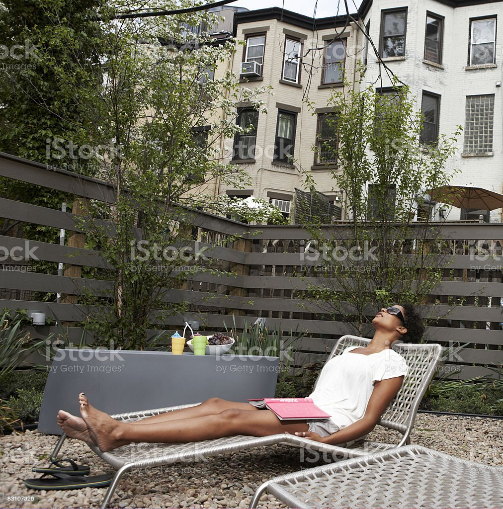 Relaxing on lounge chairs in urban backyard royalty free stockfoto