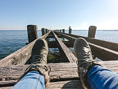 Legs of a woman in boots on a old wooden pier. POV concept.