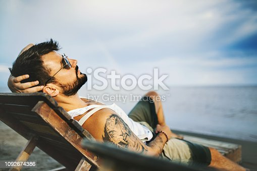 Young man relaxing on the beach during the early sunset. He's lying on the sunbed with his arm behind his head.
