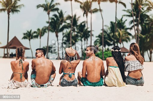 Multi-ethnic group of young people sitting on the beach