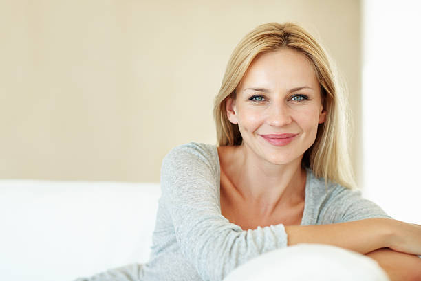 Relaxing on the couch Closeup of beautiful middle aged woman relaxing on couch at home beautiful woman stock pictures, royalty-free photos & images