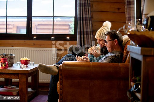 A man uses a smartphone whilst relaxing on the sofa with his wife. The woman is holding a hot drink and is wearing a bobble hat.