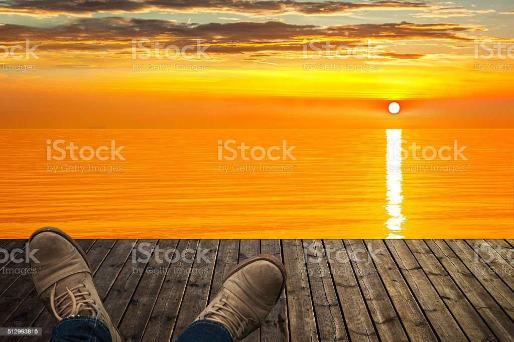 Relaxing on the wooden pier at sunrise stock photo