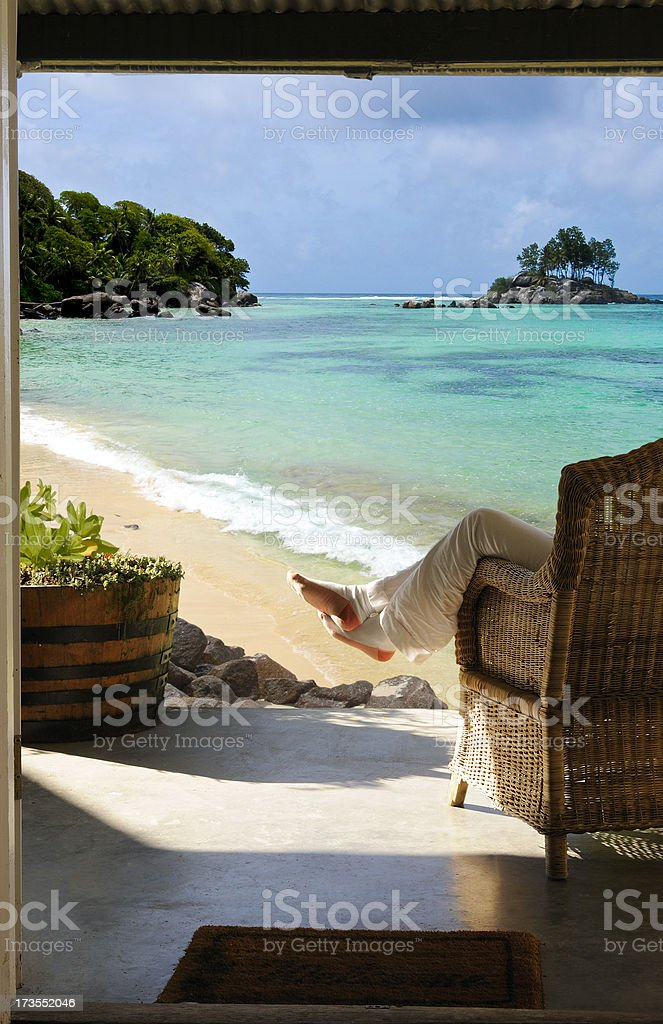Relaxing on veranda of tropical beach cottage royalty-free stock photo