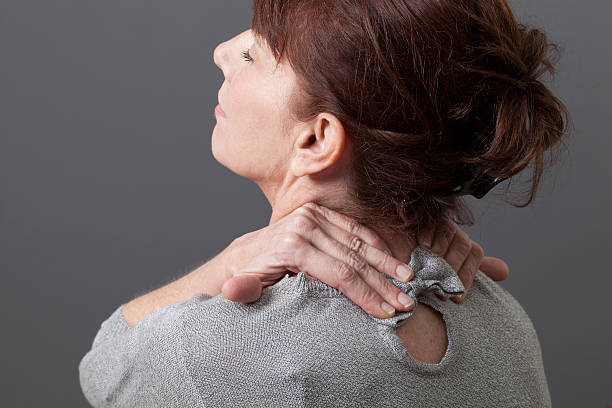 relaxing pain and pressure in neck and shoulders 50s woman leaning her head for head and backbone relaxation cervical vertebrae stock pictures, royalty-free photos & images
