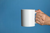 Caucasian female is holding a white coffee mug in hand in front of a blue background.