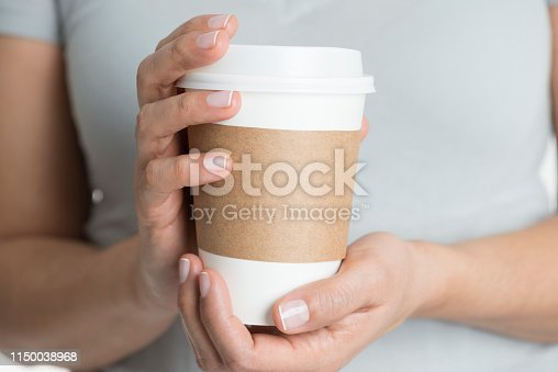 Caucasian female in gray t-shirt is holding a coffee mug in hands.