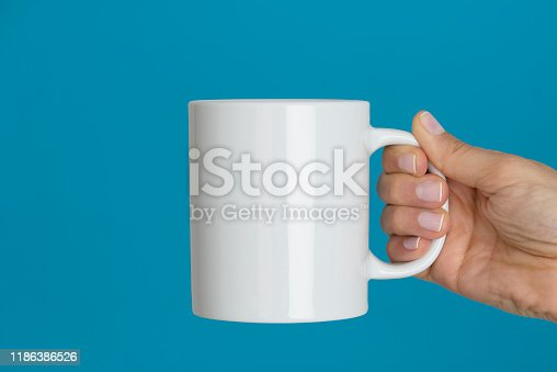 Caucasian female with nail polish is holding a coffee mug in hand.