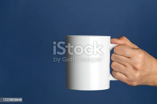 Caucasian female is holding a white coffee mug in hand in front of a navy blue background.