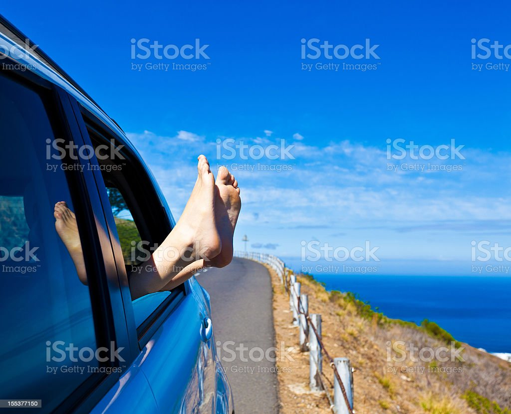 Relaxing Travel backgrounds. Bare feet out the car window at the coastline. Adventure Stock Photo