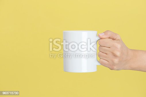 Caucasian female is holding a white coffee mug in hand in front of a yellow background.