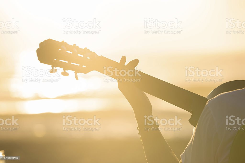 Relaxing playing guitar at sunset stock photo