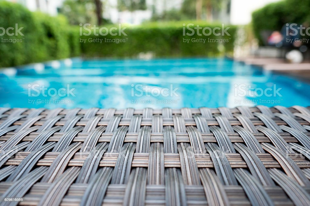 Relaxing rattan bed beside swimming pool stock photo