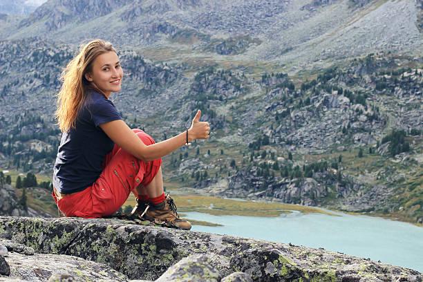 Relaxing red hair woman enjoy beautiful mountain view. stock photo