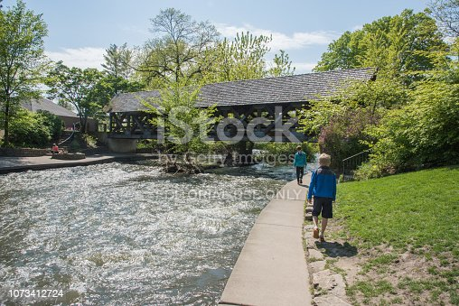 Naperville, Illinois, United States-May 6,2017: DuPage River rapids, covered bridge and people taking a leisure walk on the Riverwalk in Naperville, Illinois