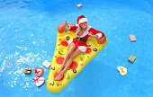 A young woman dressed in a Santa Claus suit lies in a pool on a sun bed.