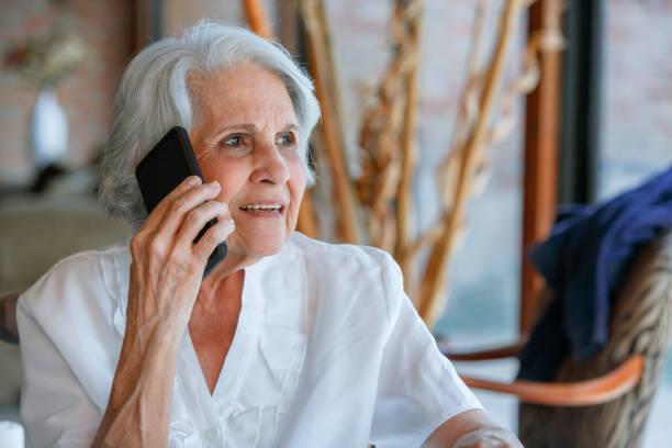 Femme âgée de détente utilisant le téléphone mobile tout en s'asseyant dans le salon - Photo