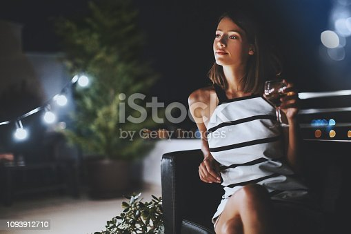 Young woman sitting and drinking white wine alone on the terrace at summer night.