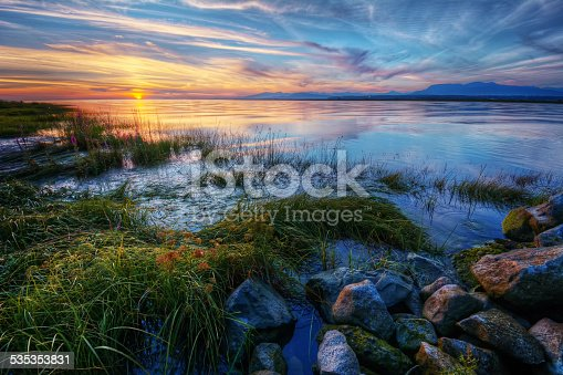 istock Relaxing summer river sunset with green grass and distant mountains 535353831