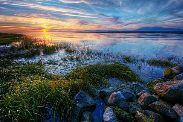 Relaxing summer river sunset with green grass and distant mountains Relaxing summer river sunset with green grass blue skies and distant mountains southern usa stock pictures, royalty-free photos & images