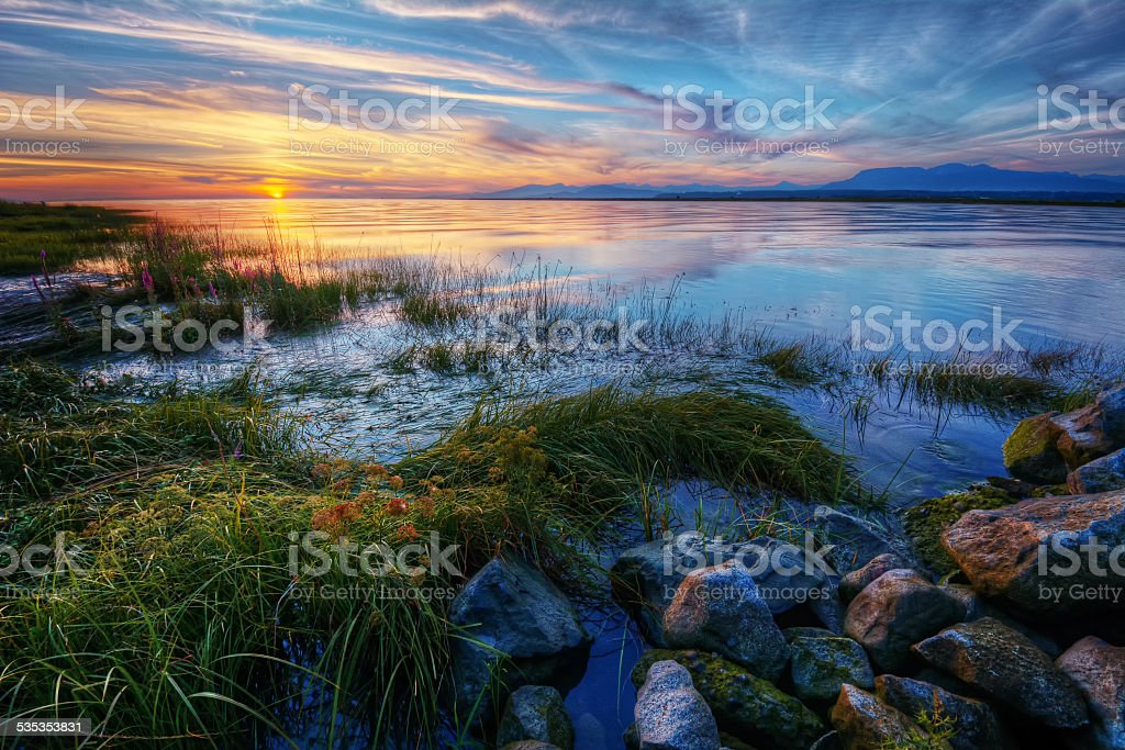 Relaxing summer river sunset with green grass and distant mountains stock photo