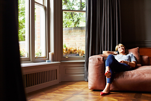 Shot of a mature woman lying back on her sofa listening to music on headphones