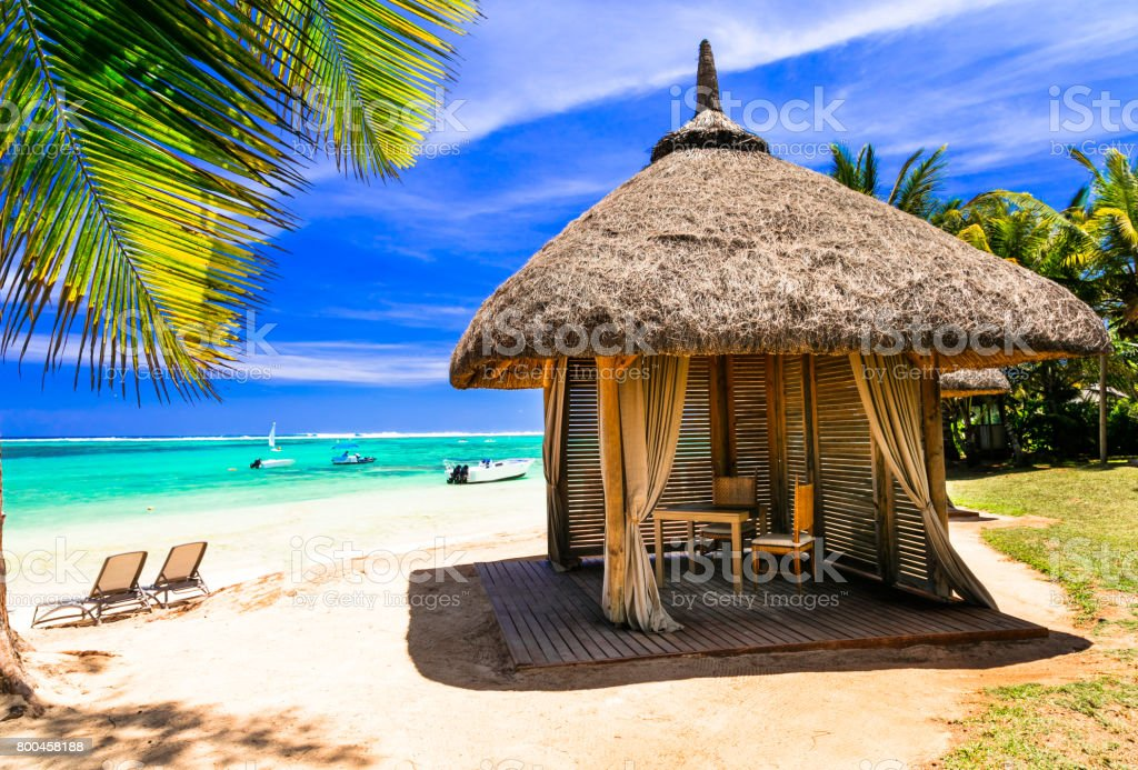 Relaxing tropical holidays. scenery with beach bungalow under palm tree stock photo