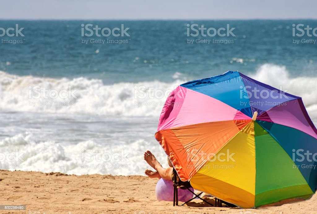 Relaxing under colorful beach umbrella stock photo
