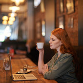 Cropped shot of a young woman sitting with her laptop at a coffee shop