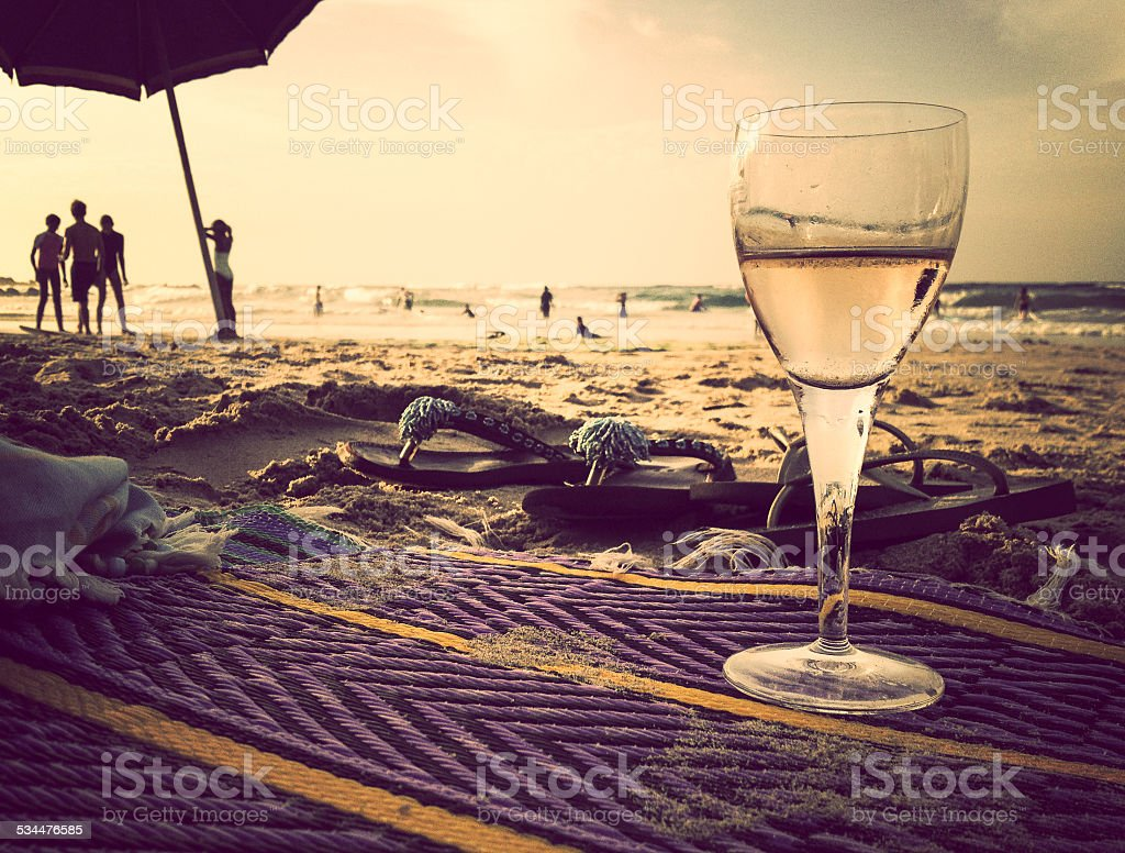 Relaxing with a glass of wine on the beach stock photo