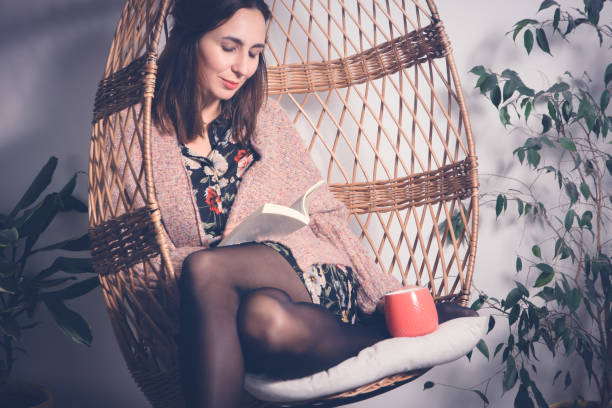 Relaxing with book in swing chair stock photo