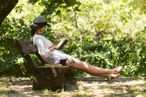 Girl sitting on bench in park shade and reading a good book