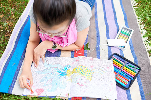 relaxing with coloring book - colouring book stock photos and pictures